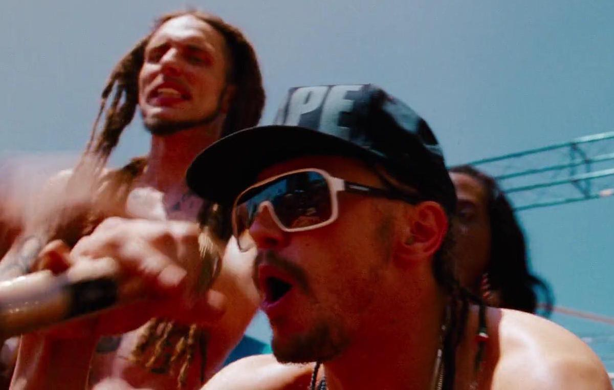 Spring Breakers Alien wears a black DOPE hat during his beach concert