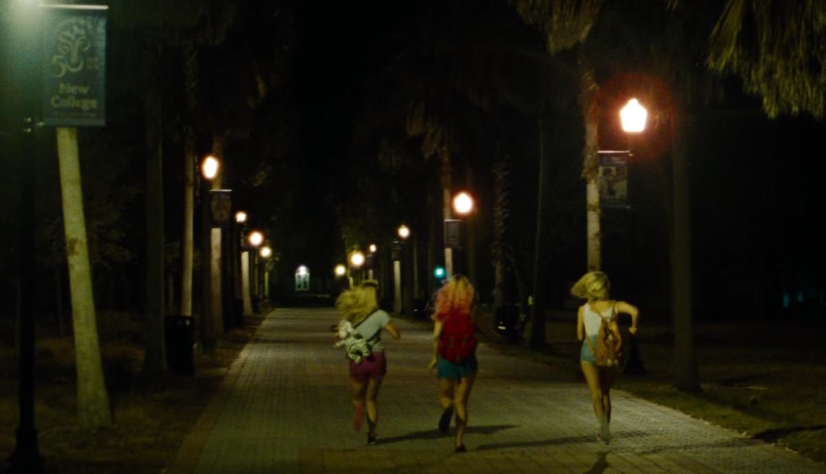 Candy wears her white baby tiger daypack while running in Spring Breakers