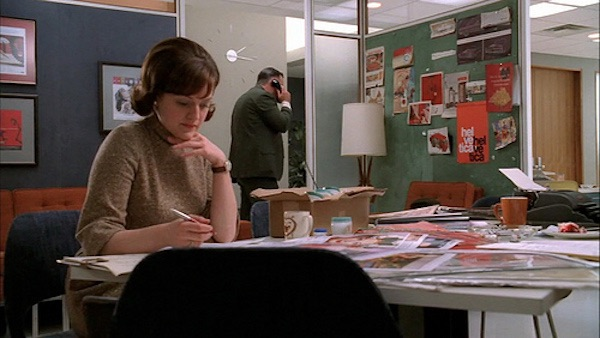 Mad Men Peggy Olson Orange Helvetica Poster hangs in the creative department in Christmas Comes But Once a Year
